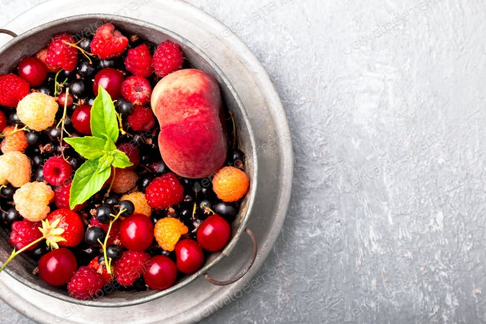 Mix fruit and berries in grey metal bowl