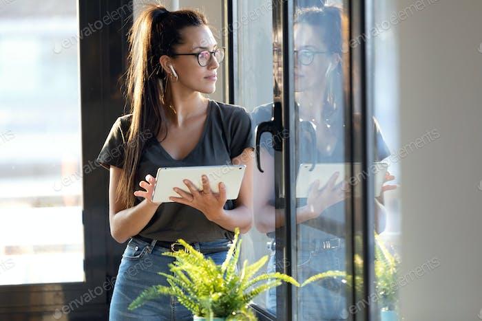 Hübsche junge Geschäftsfrau, die durch das Fenster schaut, während sie ihr digitales Tablet im Büro benutzt.