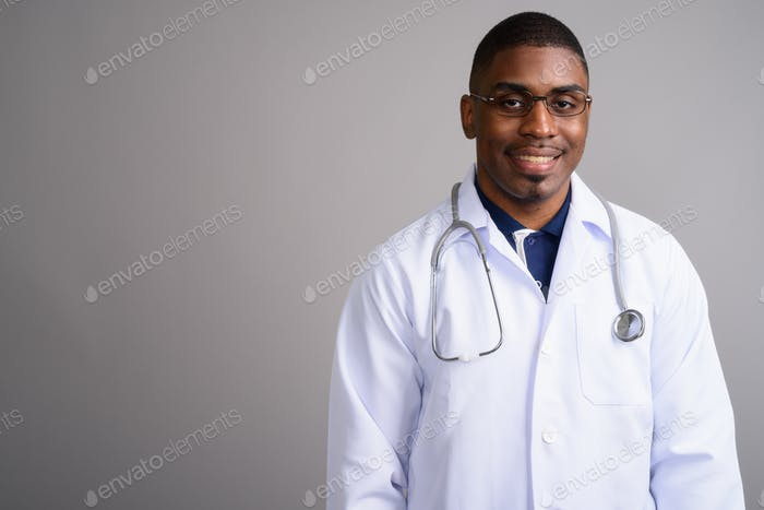 Young handsome African man doctor against gray background