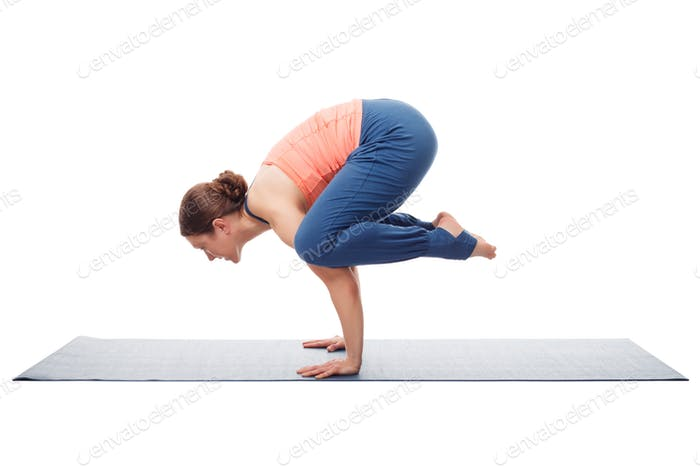 Beautiful sporty fit yogini woman practices yoga asana kakasana