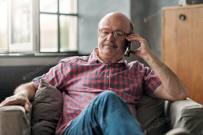 Retired hispanic man talking on phone sitting at living room.