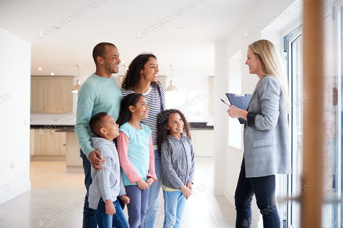 Female Realtor Showing Family Interested In Buying Around House