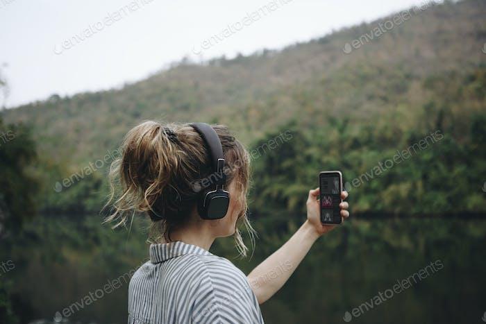Frau allein in der Natur Musik hören mit Kopfhörern und Smartphone
