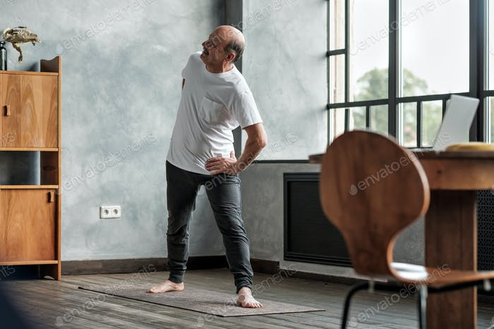 Älterer Mann praktiziert Yoga oder Fitness während Trikonasana.