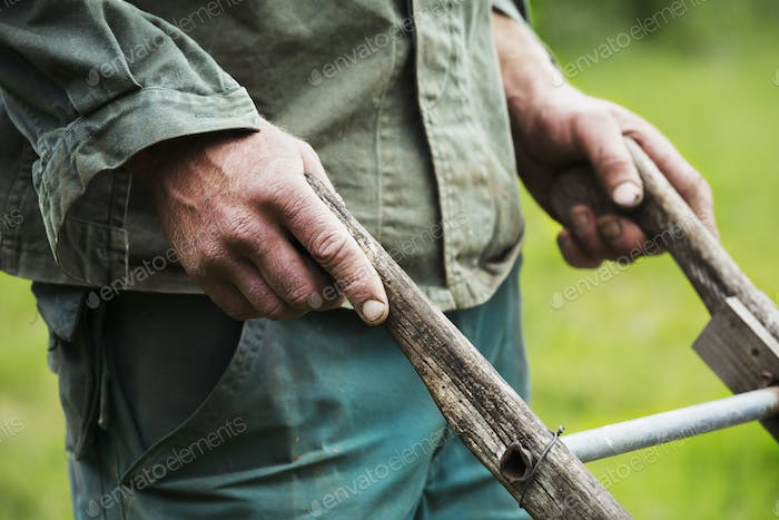 A person holding the wooden handles of a wheel hoe.