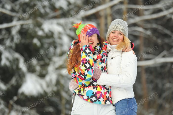 Two girls in the winter forest emotionally hug and smile.Happy women hug and Express joy