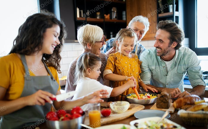 Cheerful family spending good time together while cooking in kitchen