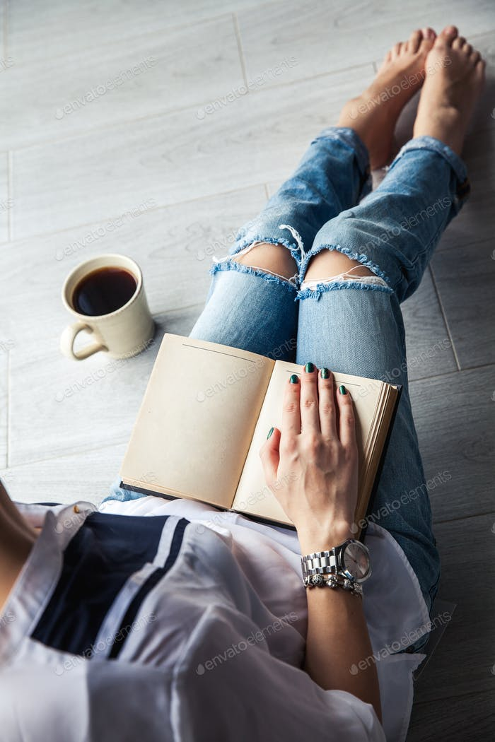 Young modern girl in torn jeans reading a book with a big cup