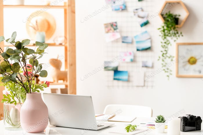 Workplace of designer with laptop, office supplies and floral compositions