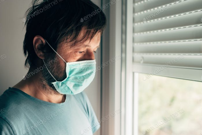 Depressed man with protective mask in self-isolation quarantine during virus outbreak pandemic
