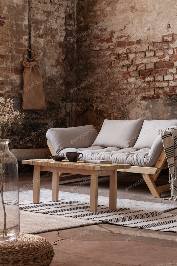 Wooden table in front of grey sofa in simple loft interior with