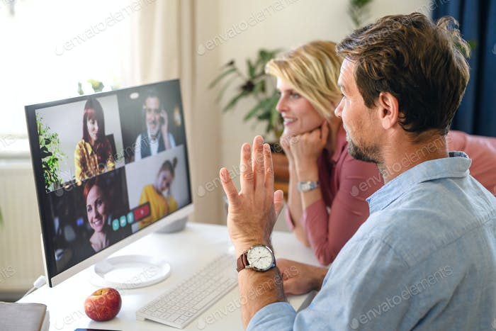 Happy couple having video call on laptop indoors at home, waving