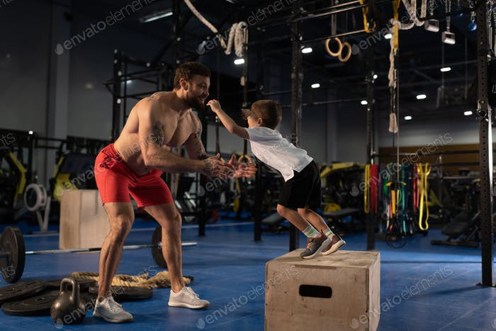 Happy father catching jumping son in gym