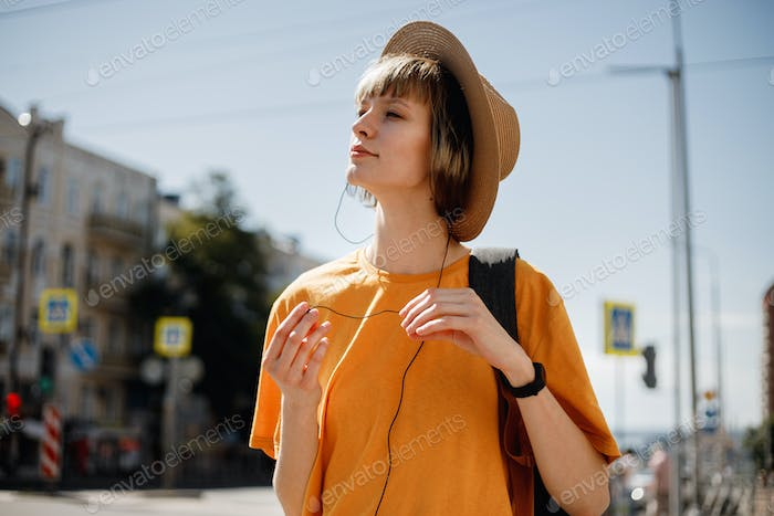 Smiling young girl with headphones dressed in a yellow t-shirt and a straw hat walks with a backpack