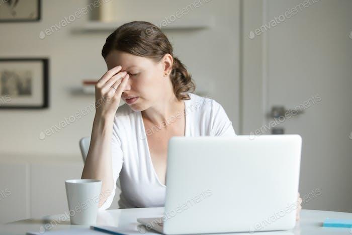 Porträt einer Frau am Schreibtisch mit Laptop, Hand an der Stirn