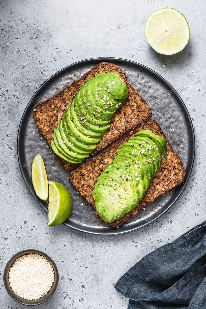 Top view on two toasts with avocado on a black plate on a table