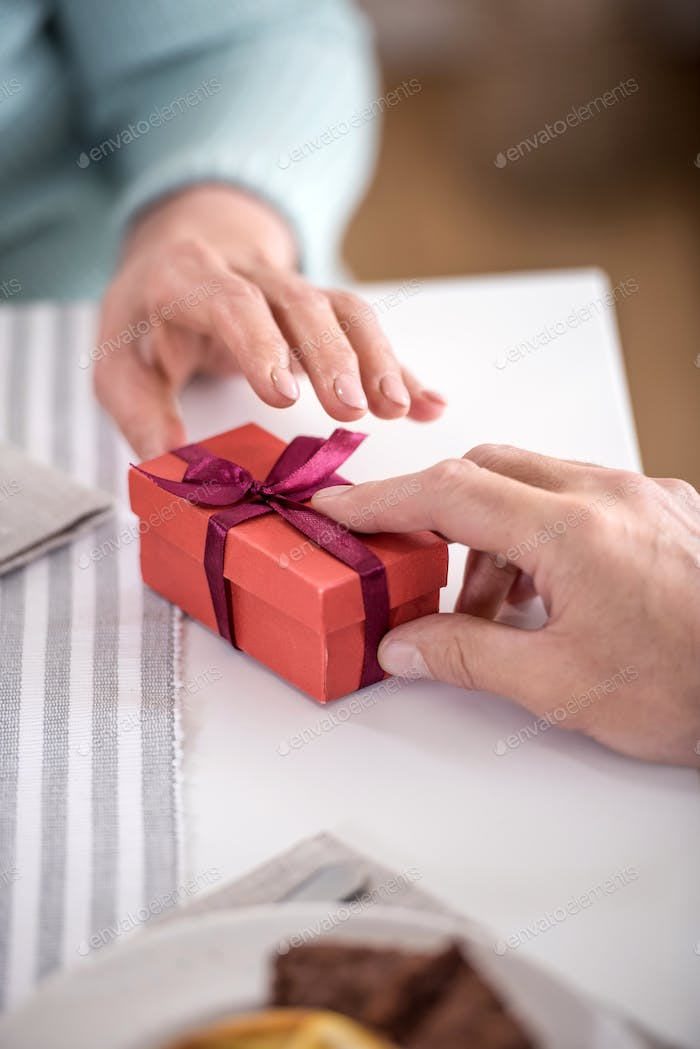 cropped shot of man presenting gift in box with ribbon to his wife