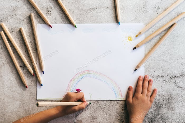 The child's hands are painted with colored pencils on a white paper.