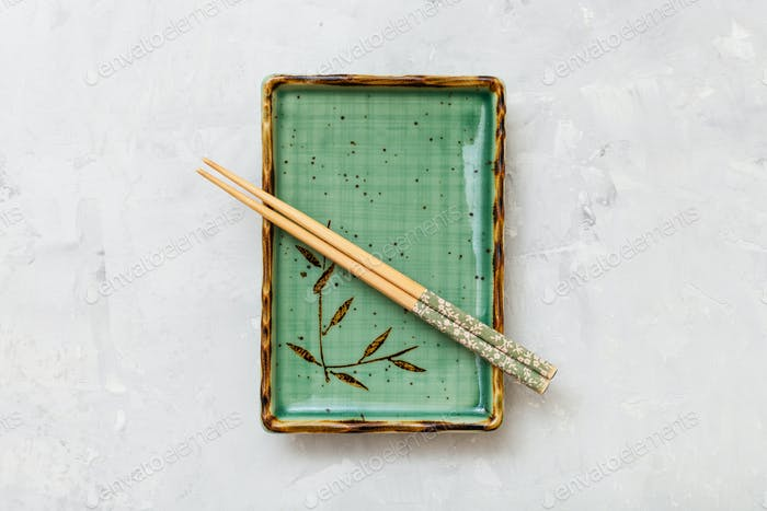 above view green plate with chopsticks on concrete