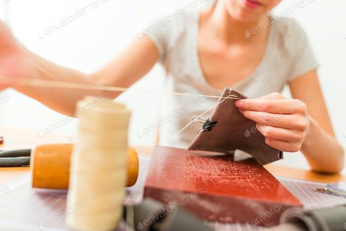 Leather craftsman making a bag