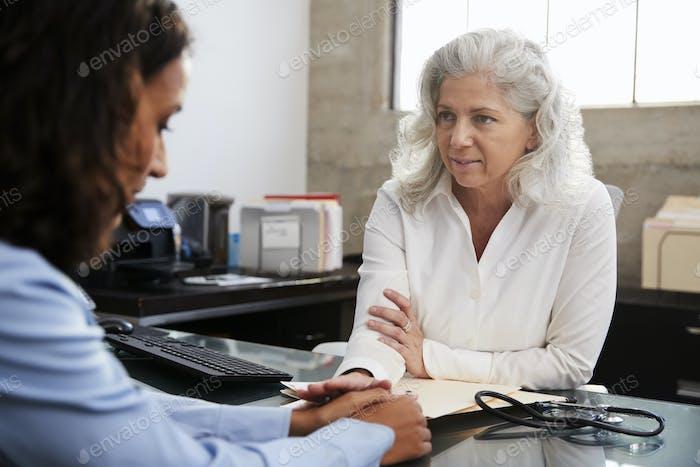 Женщина врач успокаивает пациента в консультации