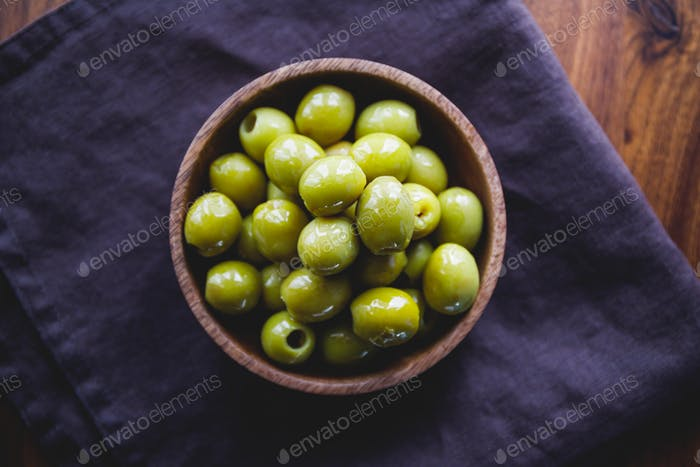 Green olives in a wooden bowl on a table, top view.