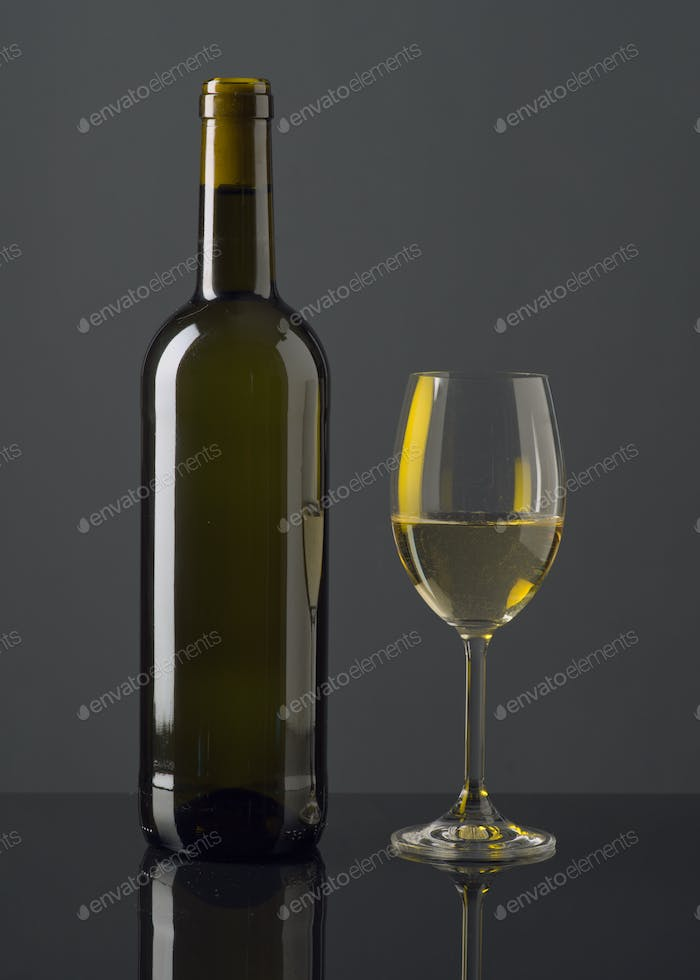 Spanish wine bottle and full glass on black glass