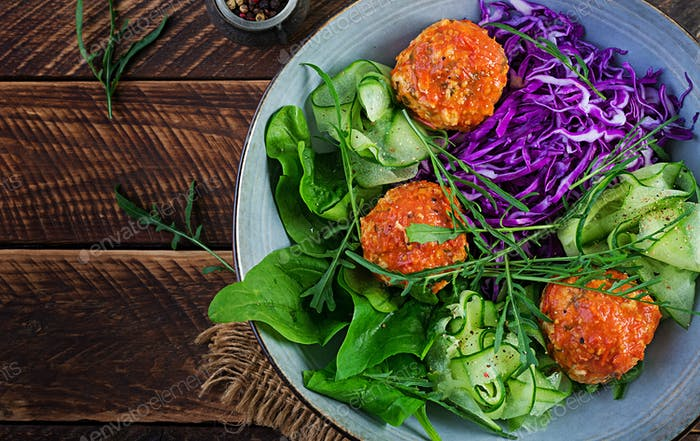 Chicken meatballs and salad on wooden background