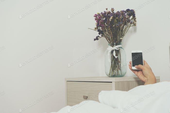 Mujeres de la Mano sosteniendo un teléfono. Flor en la mesita de noche en una luz