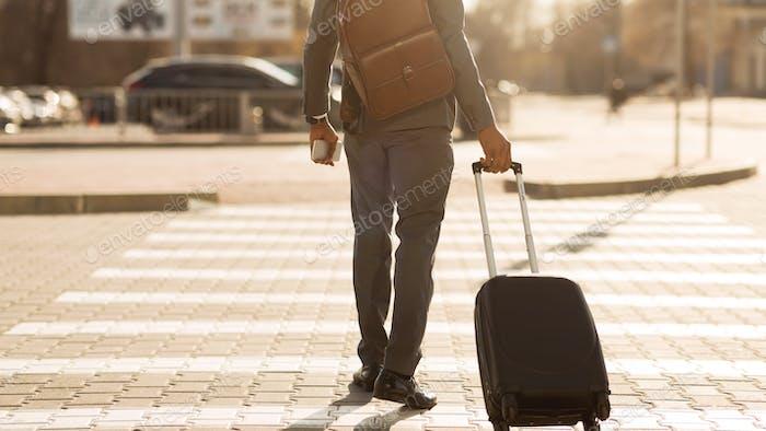 Неузнаваемый джентльмен с путешествием чемодан пересекает дорогу Открытый, Панорама, Задний вид