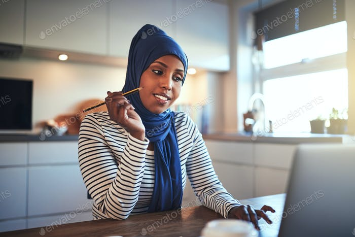 Smiling Arabic female entrepreneur working online in her kitchen