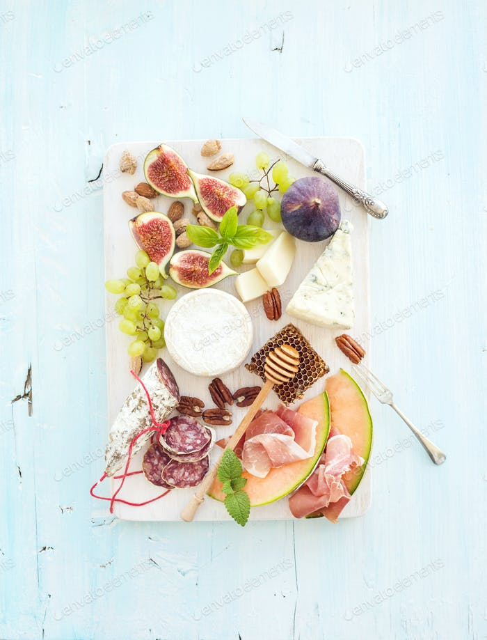 Wine snack set. Figs, grapes, nuts, cheese variety, meat appetizers and herbs