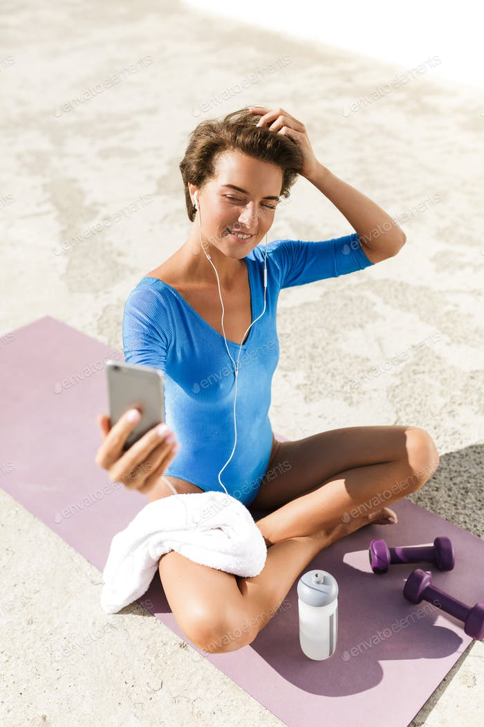 Beautiful smiling woman in swimsuit happily looking in her cellphone taking selfie while doing yoga