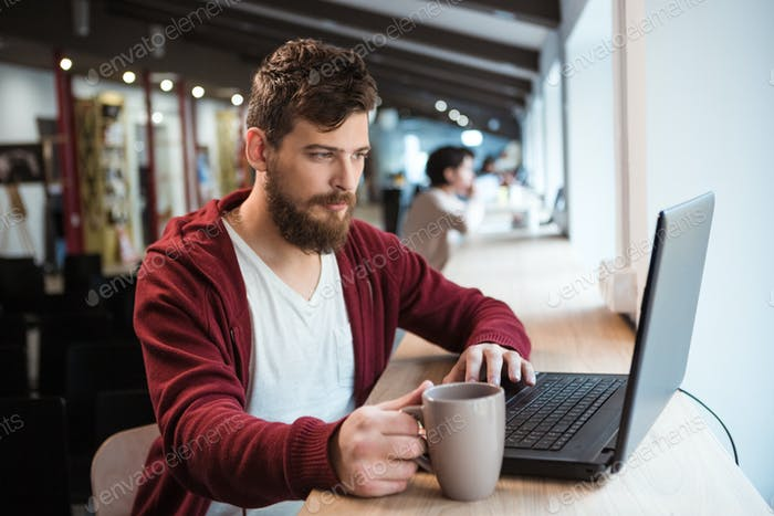 Handsome hipster using laptop and drinking coffee