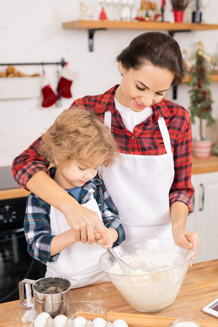 Young female helping her son whisk eggs with flour in bowl while preparing dough