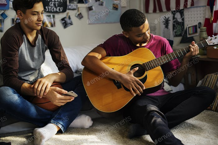 Teenage boys hanging out in a bedroom playing an acoustic guitar hobby and music concept
