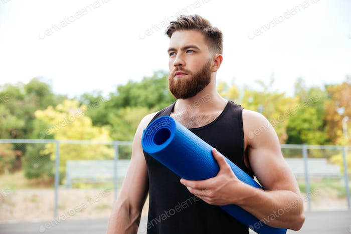 Concentrated serious male yoga instructor holding mat