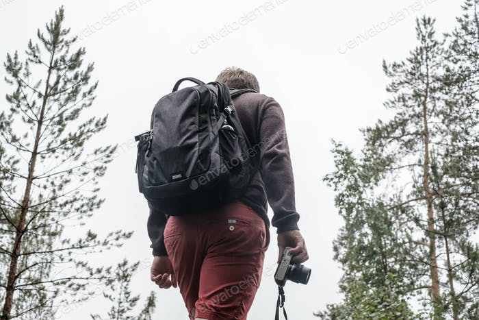 A male tourist with a backpack and a camera in his hand