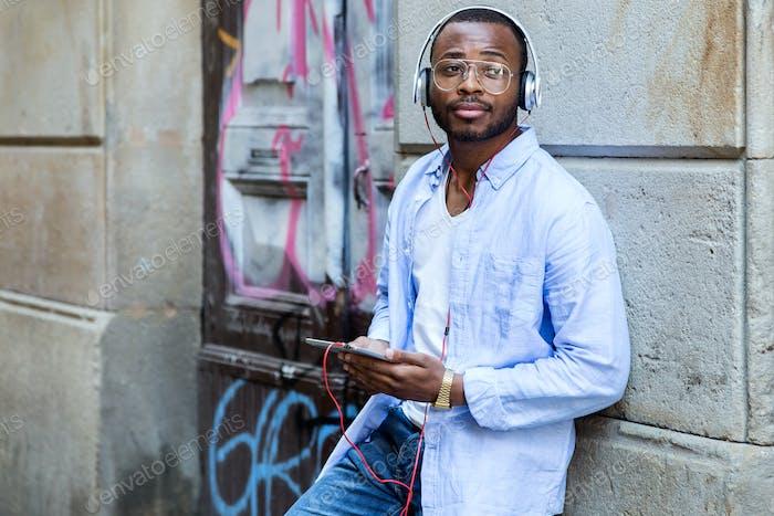 Joven guapo escuchando música con tableta digital.
