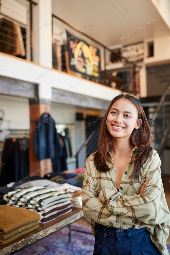 Porträt des Lächelnden Weiblichen Besitzer von Modegeschäft Stehen Vor Kleidung Display