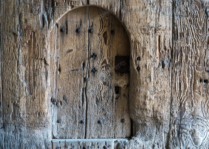 Background of weathered old rustic painted wood with a small door