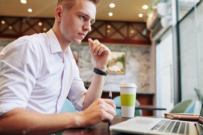 Serious businessman reading document on laptop