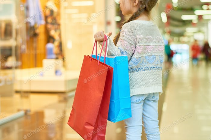 Cute Little Girl Holding Shopping Bags