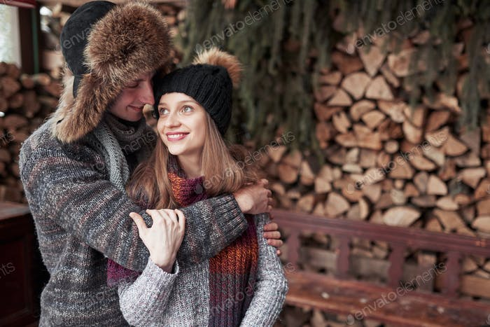 christmas and couple concept - smiling man and woman in hats and scarf hugging over wooden country