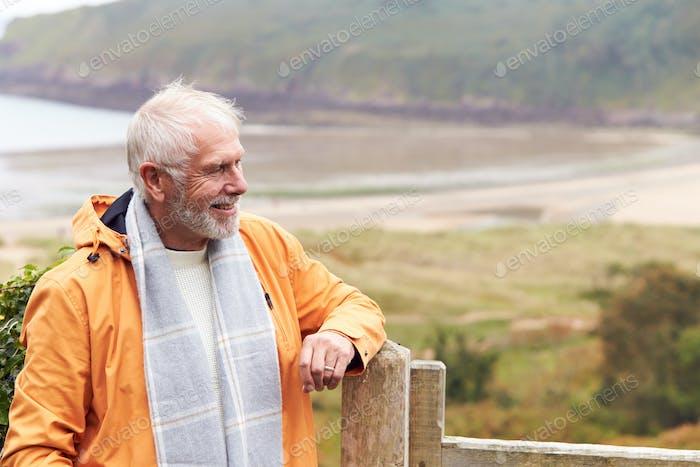 Aktive Senior Man Gehen Entlang Küstenpfad Im Herbst Oder Winter Durch Tor Mit Strand Und Klippen Hinter