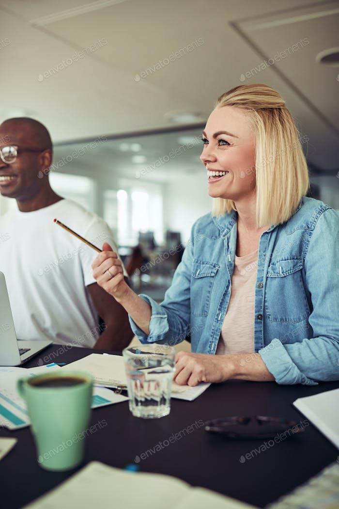 Junge Geschäftsfrau lachen während eines Treffens in einem Büro