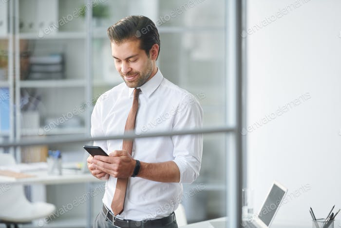 Mobile businessman scrolling through contacts in smartphone
