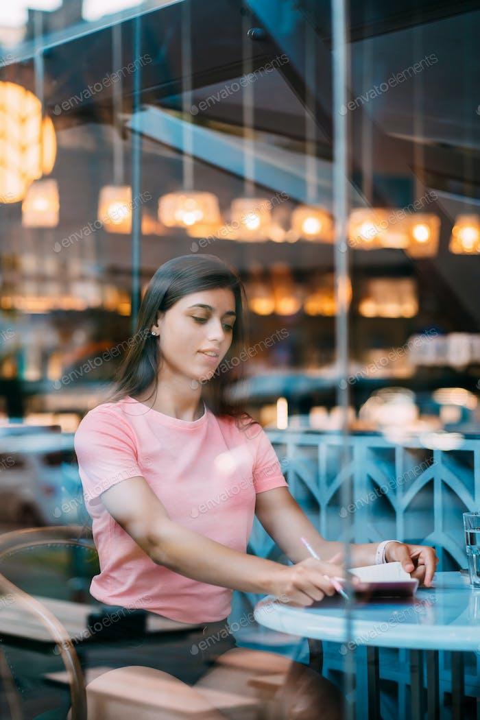 Placeit - Schöne Brünette sitzt hinter einem Fenster in einer Café-Bar