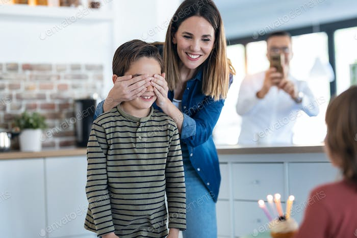 Young mother covering her son's eyes while they bring him the birthday cake in the kitchen at home.