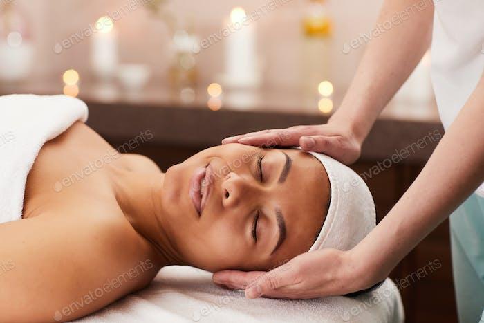 Beautiful Woman Enjoying Face Massage in Spa